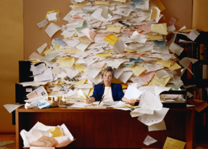 Businesswoman sitting at a desk with a large pile of paper by microsoft