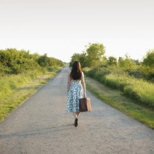 Femme avec valise sur la route